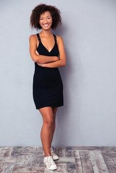 Pełnej długości portret szczęśliwej kobiety stojącej z założonymi rękoma na szarej ścianie. patrząc z przodu