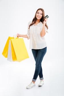 Pełnej długości portret szczęśliwej młodej kobiety trzymającej torby na zakupy i kartę bankową na białym tle na białej ścianie