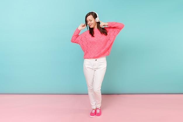 Pełnej długości portret szczęśliwej młodej kobiety w dzianinowym swetrze z różami, białych spodniach, słuchawkach