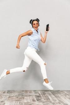 Pełnej długości portret szczęśliwej młodej kobiety w okularach przeciwsłonecznych na białym tle, trzymając telefon komórkowy, słuchanie muzyki w słuchawkach, bieganie