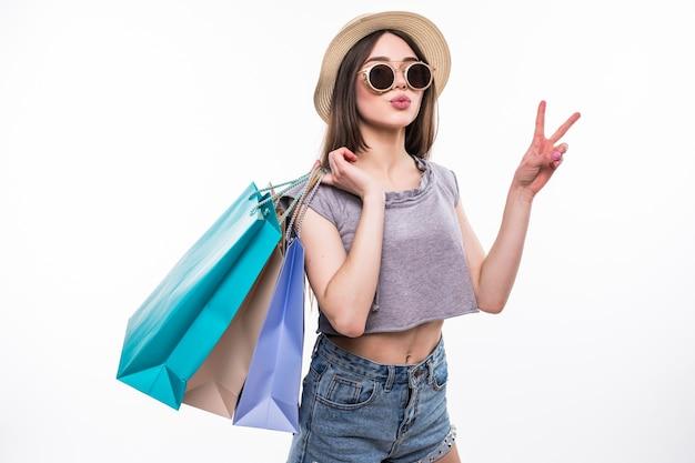 Pełnej długości portret szczęśliwej podekscytowanej dziewczyny w jasnych, kolorowych ubraniach, trzymając torby na zakupy, stojąc i pokazując gest pokoju na białym tle