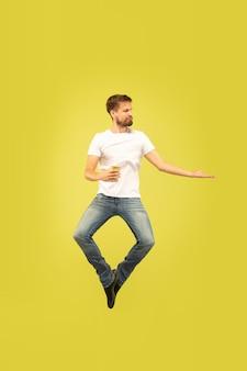 Pełnej długości portret szczęśliwy człowiek skaczący na żółtym tle