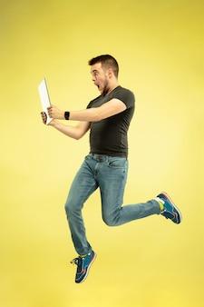 Pełnej długości portret szczęśliwy człowiek skaczący z gadżetami na żółtym tle.
