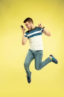 Pełnej długości portret szczęśliwy człowiek skaczący z gadżetami na żółtym tle