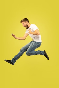 Pełnej długości portret szczęśliwy człowiek skoki na białym tle na żółtym tle. kaukaski model mężczyzna w ubranie. wolność wyborów, inspiracja, koncepcja ludzkich emocji. wygrana w zakładzie sportowym.