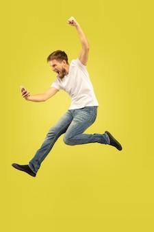 Pełnej długości portret szczęśliwy człowiek skoki na żółtym tle