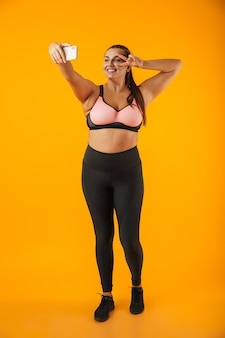 Pełnej długości portret uśmiechnięta młoda kobieta z nadwagą, ubrana w odzież sportową, stojący na białym tle nad żółtą ścianą, biorąc selfie
