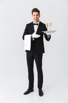 Pełnej długości portret uśmiechniętego młodego kelnera w smokingu, trzymając tacę z dwoma kieliszkami szampana na białej ścianie