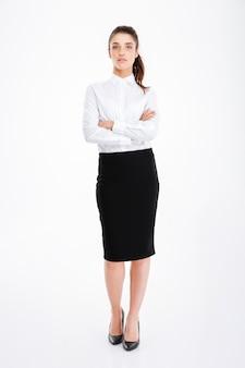 Pełnej długości portret uśmiechniętej bizneswoman stojącej z założonymi rękoma na białym tle na białej ścianie