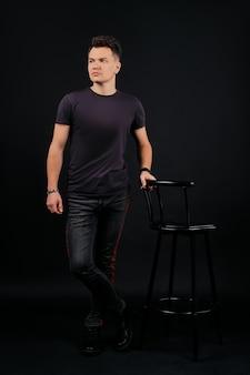 Pełnej długości portret w niskim kluczu człowieka stojącego w pobliżu krzesła
