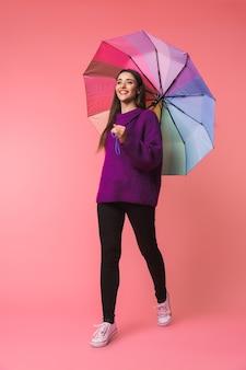 Pełnej długości portret wesoła młoda kobieta ubrana w sweter spacerujący z parasolem na białym tle nad różową przestrzenią