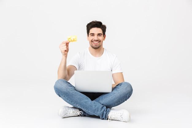 Pełnej długości portret wesołego młodego mężczyzny noszącego zwykłą odzież na białym tle nad białym, siedzącego z laptopem, pokazującego kartę kredytową, świętującego
