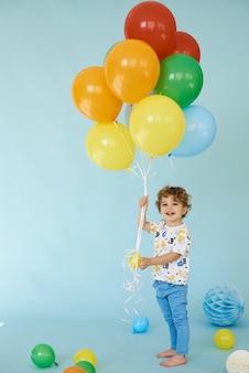 Pełnej długości portret wesoły chłopiec trzymający balony na niebieskim tle, koncepcja urodziny
