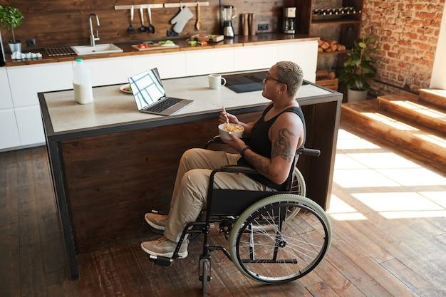 Pełnej długości portret współczesnej wytatuowanej kobiety na wózku inwalidzkim, oglądającej filmy za pośrednictwem laptopa w domu, kopia przestrzeń