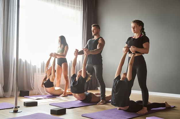 Pełnej długości portret wysportowanej grupy kobiet i mężczyzny pomagających sobie nawzajem podczas wykonywania jogi