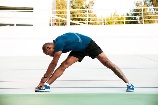 Pełnej długości portret zmotywowanego sportowca robi rozciąganie