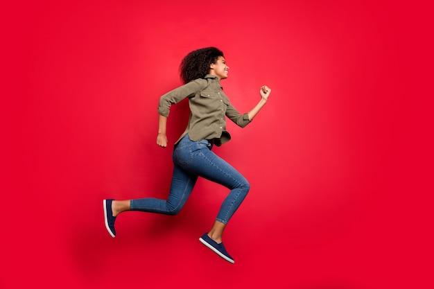 Pełnej długości profil boczny rozmiar ciała śpieszący bieganie skoki dziewczyna na sobie dżinsy koszuli noszenie obuwia z dużą prędkością na białym tle