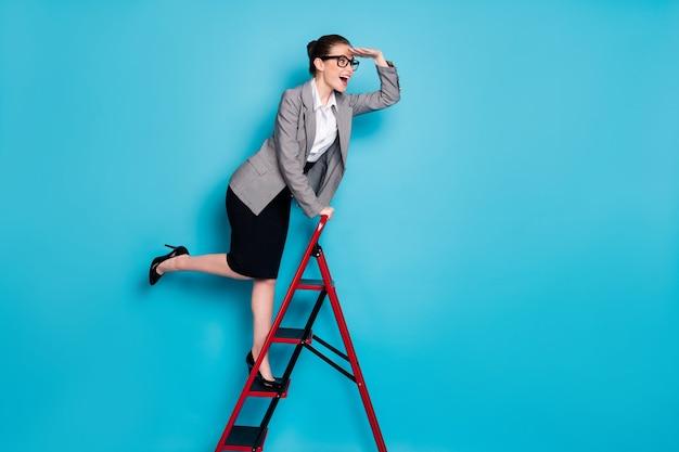 Pełnej długości profilowe zdjęcie boczne dziewczyna marketer wspinanie się po drabinie kariery ręka oczy zegarek nosić marynarka kurtka spódnica na białym tle niebieski kolor tła