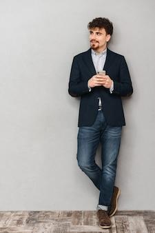 Pełnej długości przystojny, przekonany, młody biznesmen ubrany w kurtkę stojący na białym tle nad szarym, trzymając telefon komórkowy