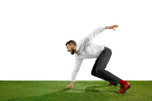 Pełnej długości strzał młodego biznesmena gry w piłkę nożną na białym tle.