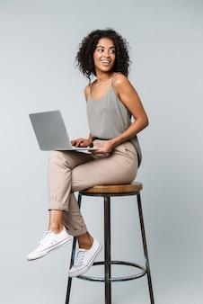 Pełnej długości szczęśliwa młoda afrykańska kobieta ubrana niedbale siedzi na krześle na białym tle, pracując na komputerze przenośnym