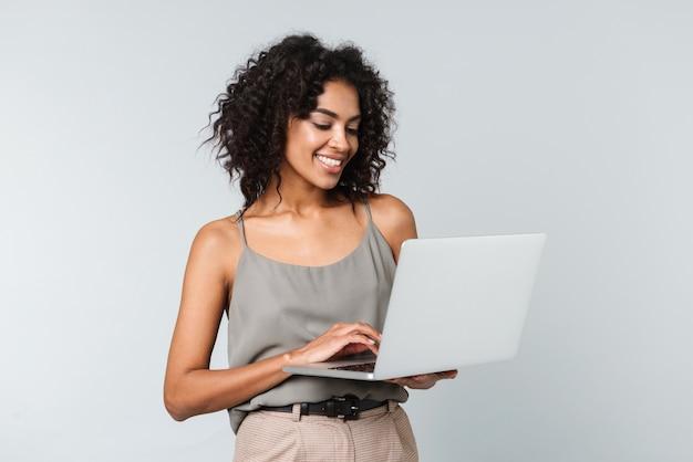 Pełnej długości szczęśliwa młoda afrykańska kobieta ubrana niedbale stojąca na białym tle, pracująca na komputerze przenośnym