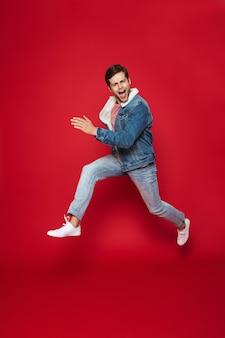 Pełnej długości szczęśliwy młody człowiek ubrany w ciepłą kurtkę dżinsową skoki na białym tle nad czerwoną ścianą
