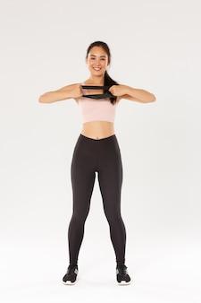 Pełnej długości szczupła i dopasowana ładna azjatka wykonująca ćwiczenia fitness, rozciągająca opór z rękami i uśmiechnięta. trener przy użyciu sprzętu do ćwiczeń w siłowni, biała ściana