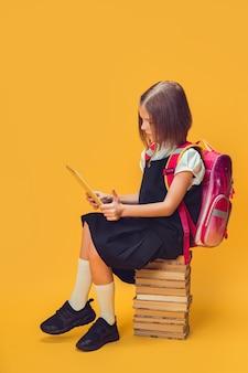 Pełnej długości uczennica w mundurze siedzi na stosie książek pracuje nad koncepcją edukacji dla dzieci na tablecie