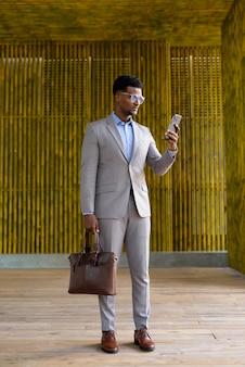 Pełnej długości ujęcie afrykańskiego biznesmena na zewnątrz przy użyciu telefonu komórkowego