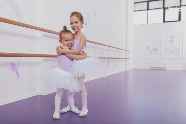 Pełnej długości ujęcie dwóch uroczych małych baletnic i spódnic tutu i trykotów przytulających, uśmiechających się do kamery, miejsce