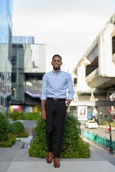 Pełnej długości ujęcie przystojnego czarnego afrykańskiego biznesmena na zewnątrz w mieście podczas letniego ujęcia pionowego