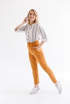 Pełnej długości uśmiechnięta blond kobieta w okularach chodząca i rozmawiająca przez telefon komórkowy na białym tle nad białą ścianą