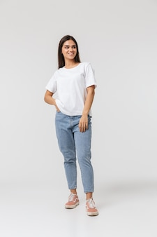 Pełnej długości uśmiechnięta młoda kobieta ubrana casualy stojącej na białym tle
