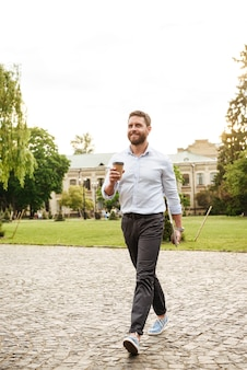 Pełnej długości uśmiechnięty mężczyzna w wizytowym stroju, spacerujący po parku z kawą na wynos i srebrnym laptopem