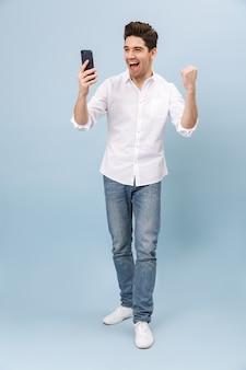 Pełnej długości wesoły przystojny młody człowiek stojący na białym tle na niebiesko, trzymając telefon komórkowy, świętuje