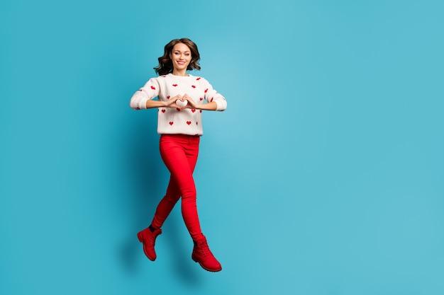 Pełnej długości widok ładnej, atrakcyjnej, uroczej, wesołej dziewczyny skaczącej w świątecznych ubraniach na imprezę tematyczną ze znakiem serca