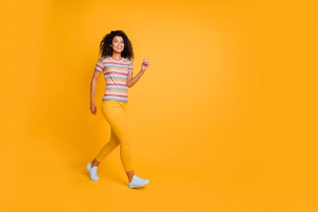 Pełnej długości widok wielkości ciała dziewczyny idącej biegnącej z uśmiechem wygląd aparatu