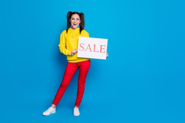 Pełnej długości zdjęcie atrakcyjne śmieszne pani dwa ogony trzymać ręce papier afisz sprzedaż zakupy baner sprzedawca nosić dorywczo żółta bluza z kapturem sweter czerwone spodnie na białym tle niebieski kolor tła