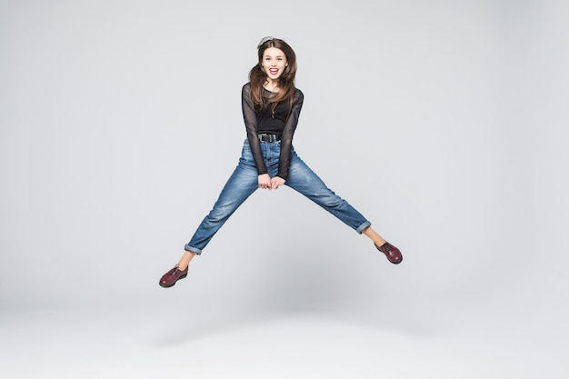 Pełnej długości zdjęcie atrakcyjnej kobiety skaczącej w powietrzu z wyciągniętymi rękami. biała ściana.