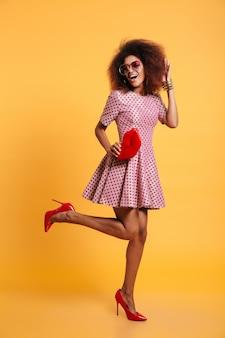 Pełnej długości zdjęcie dość afrykańskiej stylowej kobiety retro w sukience i buty na obcasie z dużymi czerwonymi ustami