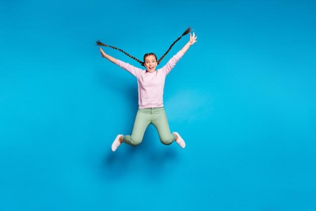 Pełnej długości zdjęcie dość szalonej pani długie warkocze latające skoki wysoko radość czas wolny beztroski nastrój nosić swobodny różowy sweter zielone spodnie izolowane niebieskie tło