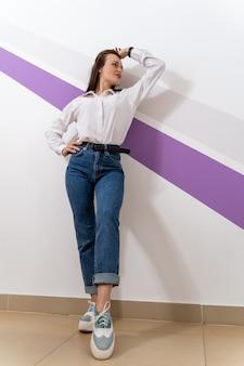 Pełnej długości zdjęcie dziewczyny w białej koszuli i niebieskich dżinsach. kobieta stoi przy białej ścianie z fioletowym paskiem. ręka nad głową.