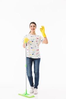 Pełnej długości zdjęcie kaukaskiej gospodyni domowej w wieku 20 lat w żółtych gumowych rękawiczkach do ochrony rąk mycie podłogi mopem na białym tle nad białą ścianą
