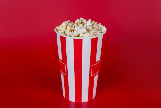 Pełnej długości zdjęcie kolorowego prostego zdjęcia torby pełnej świeżego popcornu na białym tle w jasnym kolorze