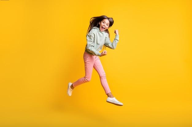 Pełnej długości zdjęcie małych ludzi podskakuje pięścią w górę tak osiągnięcia modna bluza z kapturem na żółtym tle