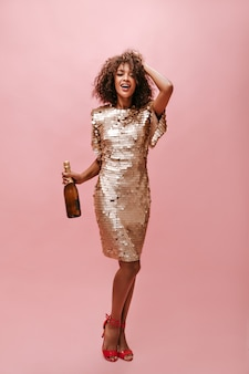 Pełnej długości zdjęcie modnej kobiety z brunetką kręconymi włosami w błyszczącej sukience i czerwonych szpilkach uśmiecha się i trzyma butelkę z napojem na różowej ścianie ..