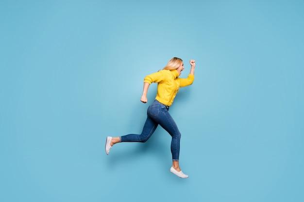 Pełnej długości zdjęcie niesamowitej blond pani skaczącej wysoko w pośpiechu zniżki niskie ceny zakupy nosić dzianiny żółty sweter dżinsy na białym tle niebieski kolor ściany