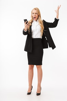 Pełnej długości zdjęcie niezadowolonej bizneswoman w garniturze biurowym krzyczy na smartfonie, na białym tle