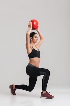Pełnej długości zdjęcie poważnej skoncentrowanej sportsmenki, patrząc na bok i wykonując ćwiczenia lonży podnoszącej piłkę fitness, na białym tle nad szarą ścianą